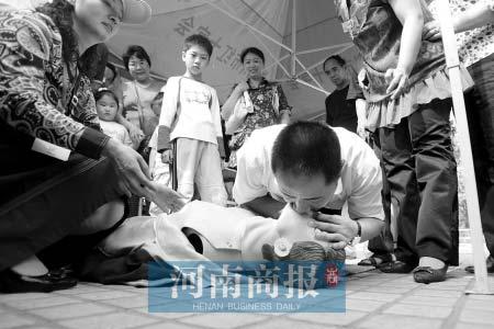 在急救知识教授现场,郑州市副市长黄保卫学做人工呼吸  商报记者 王春胜/摄