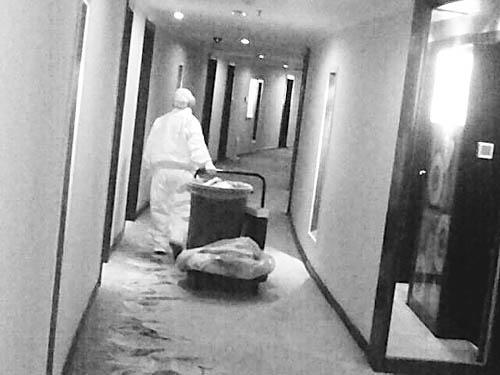 5月11日,专门接收被隔离观察者的成都某宾馆内,工作人员在清理废弃物。李健摄