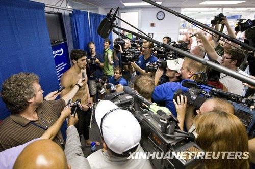 5月15日,美国选手菲尔普斯(中)在男子100米蝶泳比赛后接受记者采访。