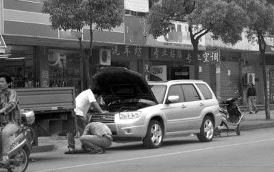 一辆日本某品牌的轿车在路边接受改装。 晨报记者 吴 磊 现场图片