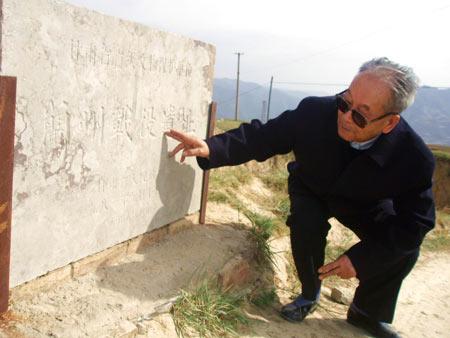 每一次上山,康明德这般抚摸这块标明解放战争遗址的碑文