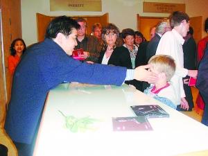 李飚与索要签名的小观众交流。