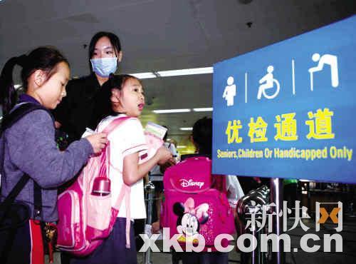 深圳罗湖口岸的检疫人员在优检通道入口疏导从香港放学回深圳的走读学童入境。