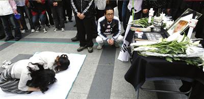 23日,在韩国首尔街头临时搭建的祭坛前,一对母女悼念韩国前总统卢武铉。新华社/路透