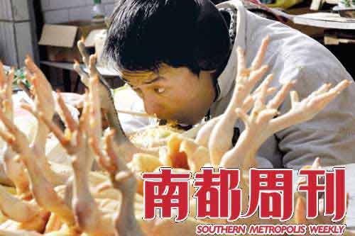 2009年1月22日,云南昆明,一名出售鸡肉的商贩正在吃午饭。