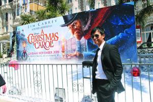 陈思成在戛纳街头的电影宣传海报前留影