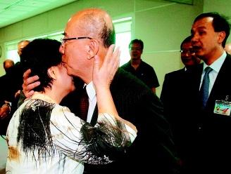 吴伯雄搭机飞北京前深情吻别妻子,送行的国民党副主席朱立伦(右)看到这个难得镜头,张大嘴表情惊讶。