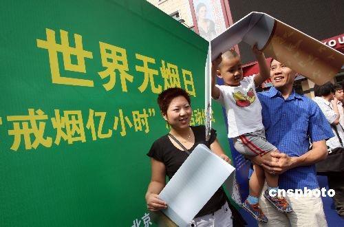"""5月29日,一个家庭在北京王府井大街将香烟模型撅断,这是由北京市爱卫会主办的世界无烟日暨""""戒烟亿小时""""公益活动现场。中新社发张宇摄"""