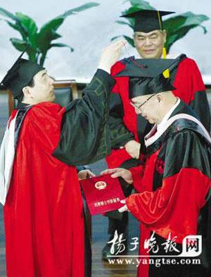 陈骏校长为吴伯雄挑正流苏。 吴俊 摄