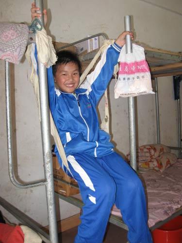 """返乡学生黄勉坐在宿舍里自制的""""秋千""""上,他已适应乡村的生活"""