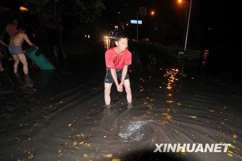 6月7日晚上,市民在柳州市西环路疏通下水道。新华社发