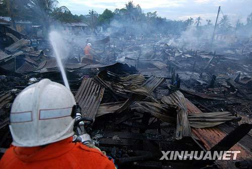 6月10日,在东马来西亚沙巴州的基纳鲁特,消防人员在火灾现场灭火。当日凌晨,基纳鲁特地区一移民聚集区发生火灾,80多幢房屋被毁,400多人失去住所。新华社发