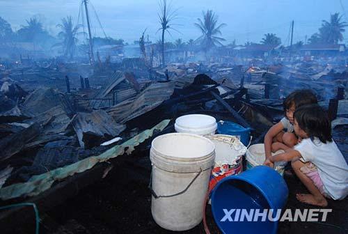 6月10日,在东马来西亚沙巴州的基纳鲁特,两名儿童蹲在火灾现场。新华社发