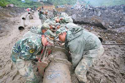 昨日,武警战士在搬运铺设堰塞湖应急排水管道用的塑胶水管新华社