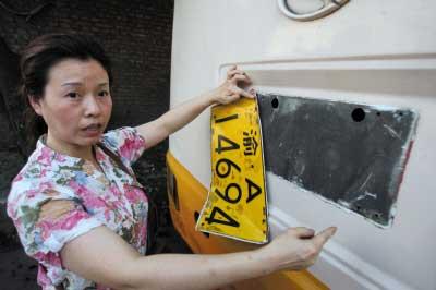 刘女士拿着被敲落的车牌讲述经过 记者 张路桥 摄