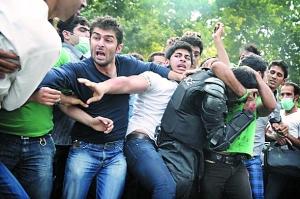 示威者在街头围殴警察(穿黑衣者)。