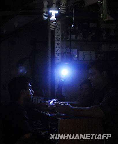 6月17日,在巴基斯坦港口城市卡拉奇,一位摊主用手电筒照明营业。新华社/法新