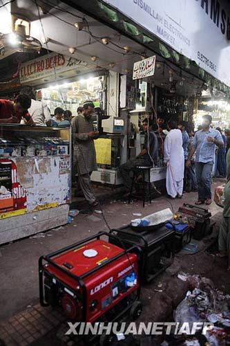 6月17日,在巴基斯坦港口城市卡拉奇,摊主用发电机发电照明。新华社/法新