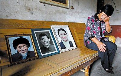 大足县雍溪镇红星街区,李明华在公公、老伴及儿媳3名亲人的遗像前哭泣