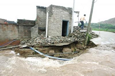 渝北区长河村,一房屋旁的路基被大水冲垮