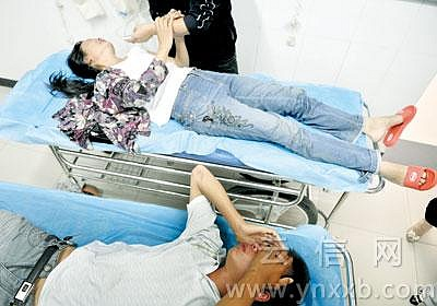 担架上的母亲拉住记者的手泣不成声,旁边的儿子一言不发,掩面痛哭。摄影:本报记者 杨映波
