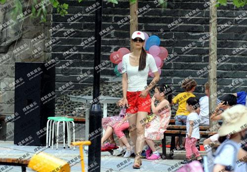 6月中,马艳丽与女儿穿着母子装在街边一起做游戏,大秀亲情。