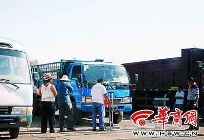 """昨日下午,三名""""车托""""正在给车辆安检,检测站副站长苏世平(右一)站在一旁 记者华新摄"""
