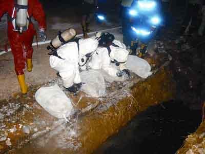 6月23日晚,现场抢险人员正将运来的石灰倒入土坑中