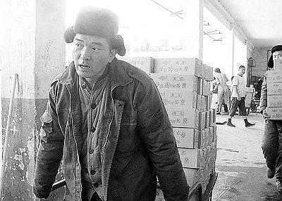 因为要频繁进出冷库,工人们都穿着厚厚的棉衣干活。(王帅军 摄)