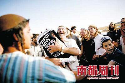 6月4日,约旦河西岸城市拉马拉附近的Maoz Ester,在以色列警察第二次摧毁当地的犹太人定居点后,一名犹太定居者怀抱圣经卷轴异常悲愤。