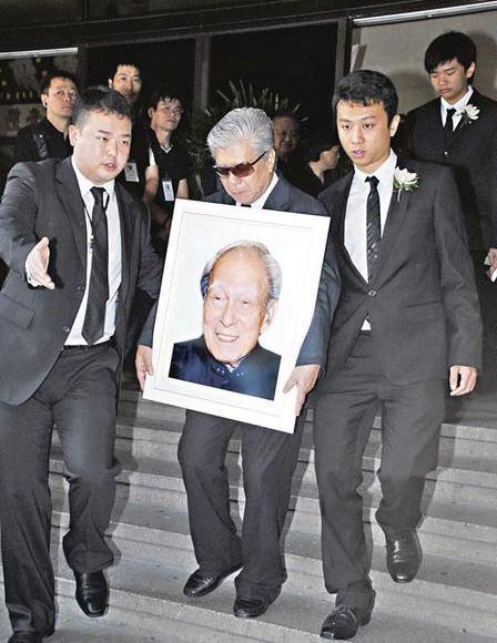 石坚儿子捧着亡父的遗照一脸哀伤,令人心酸。