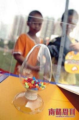 6月21日,在广州海珠区宝岗体育场的禁毒宣传现场,两名孩子在观看一瓶摇头丸样品。摄影・赵炎雄