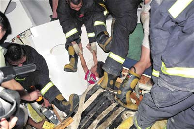 消防人员从事故列车中救出一名小男孩。《长沙晚报》供图