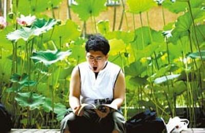 台湾指考第二天,闷热的天气让人昏昏欲睡,一名考生在荷花池边忍不住打起哈欠,但手中仍拿着书不放。图片来源:台湾《中国时报》