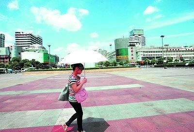 昨日上午11时许,长沙火车站广场上行人寥寥无几,一名打着太阳伞的女子在广场上匆匆走过。当日小暑,长沙迎来了新一轮高温天气。贺文兵摄