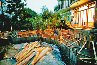 一小区业主为改风水将门前绿地挖成池塘