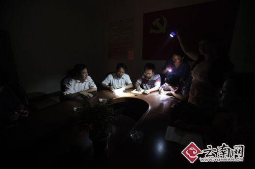 姚安县政府紧急会议现场突然断电,打着手电筒继续部署。记者 周明佳摄
