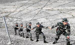 巡逻时因为风太大,战士们要手拉手地前进