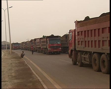 距离天津港不远的一个专门储存铁矿石的装卸场,等着排队进场的运输车排起了长龙。