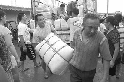 广元火车站干部职工自发地向因洪水中断铁路和公路而滞留在广元的旅客送水、送药…… (新华社)
