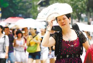 昨日,解放碑热浪袭人,市民用扇子遮挡烈日。本报首席记者 罗伟 摄