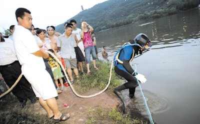 昨日,照母山植物园水库,打捞公司的蛙人正准备下水探摸 记者 刘嵩 摄