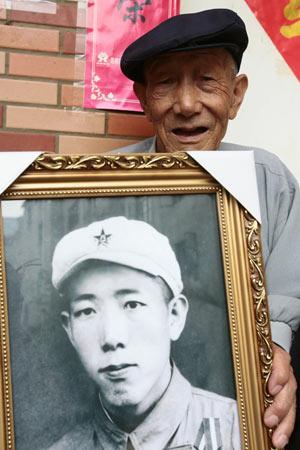 耿桓老人拿着参军时的老照片讲述解放昆明经过