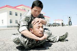 边防战士在演练中将对手摔到地上,并用手臂勒住对方头部