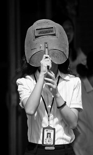 为防止眼睛被灼伤,广东佛山一导游拿着电焊专用面罩观看日偏食。 国新供图