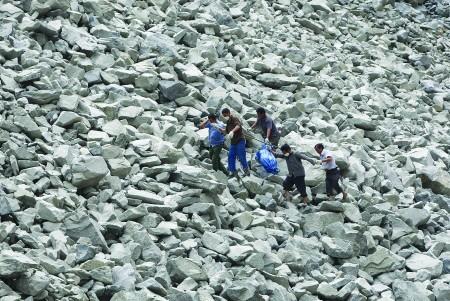 图:救援人员在乱石中抬出第一具遇难者遗体。