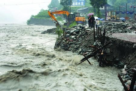 图:7月23日,国道318线天全县紫石乡小仁烟村段,道路被洪水冲毁。(《成都商报》供图)