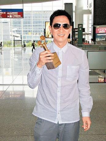 张家辉昨日返港,拿着从韩国夺得的影帝奖座让记者拍照。