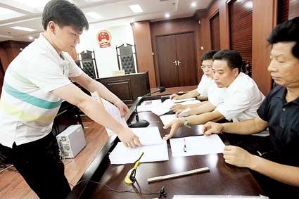 周成宇(左一)向被告方出示证据材料 摄/记者曹博远