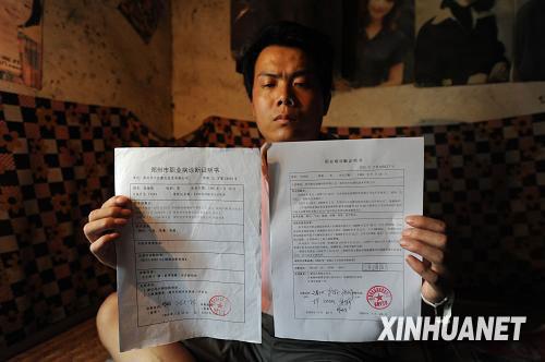 7月27日,张海超展示一份新的诊断证明书(右),这张证明书与之前的诊断证明结论不同。新华社记者赵鹏摄